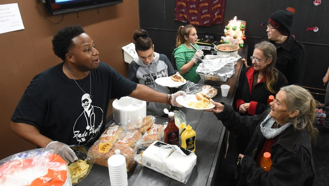 Antonio Wilborn Jr, owner of Fade Physician in downtown Zanesville, serves food during an event for the needy Wednesday evening.