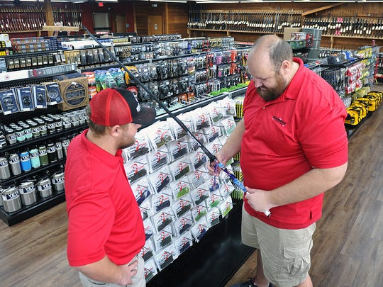 Jason Lavender, right, and Mitchaletty Baio check out a Favorite fishing rod in the Marksman Firearms and Outfitters which opens Saturday December 2. The new store carries rifles, shotguns, handguns, ammo, cleaning supplies, crossbows and has an in-house gunsmith.