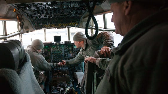 Master Sergeants Michael Baron (from right), Jose Irazarry Jr. and Jeff Dillon perform maintenance on a C-130 at the Delaware Air National Guard base.