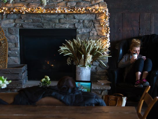 Grace Harris stays warm next to the fireplace at Brew