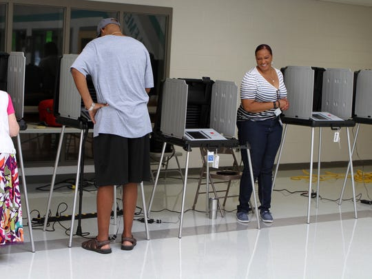 Voting Machine Operator Ambra Rivera watches as voters