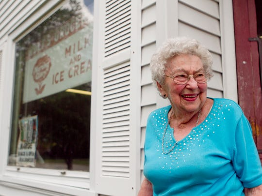 Marge Wolf stands in front of Wolf's Grocery Store