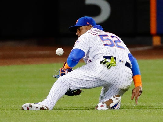 New York Mets left fielder Yoenis Cespedes (52) fails to catch a ball hit by Philadelphia Phillies' Michael Saunders for an RBI single during the eighth inning of a baseball game, Wednesday, April 19, 2017, in New York. (AP Photo/Frank Franklin II)