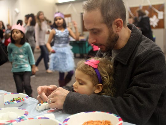 "Two-year-old Natalie Lederman and her father Adam of East Brunswick make an ""Olaf"" snowman using marshmallows and candy during a ""Frozen"" Party and coat drive hosted by the The Harry Potter Alliance, Sunday, January 4, 2015, at the East Brunswick Public Library. Jason Towlen/Staff Photographer"