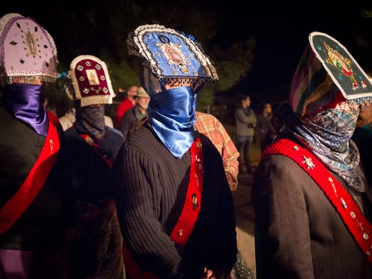 Los Danzantes, traditionally male dancers of Moorish-Hispanic origin, wait outside the Casa del Pueblo on Thursday evening as part of Tortugas Pueblo's three day Our Lady of Guadalupe Fiesta.