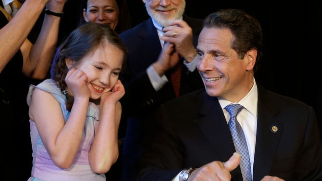 Gov. Andrew Cuomo, right, gets some help from Amanda Houser, 10, while signing a ceremonial bill to establish a medical marijuana program in New York in July.  Houser, who has Dravet syndrome, may benefit from medical marijuana.