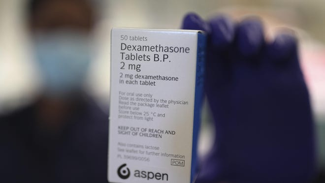 A member of staff at a pharmacy in London holds a packet of anti-inflammatory drug dexamethasone, which has been hailed as a ground-breaking treatment for hospital patients seriously ill with COVID-19. Researchers have found that the drug reduces deaths by up to a third among patients on ventilators and by a fifth for those on oxygen.
