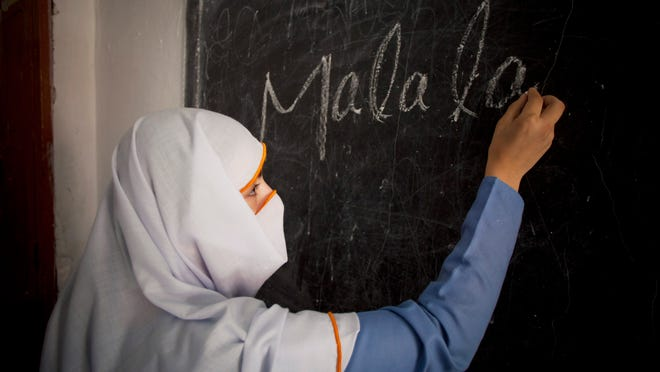 A student writes the name of Taliban attack survivor Malala Yousafzai, the youngest Nobel winner, at a school in her hometown of Swat, Pakistan, Saturday, Oct 11, 2014.