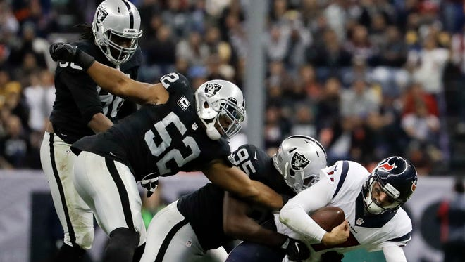 Houston Texans quarterback Brock Osweiler is hauled down by Oakland Raiders defensive end Jihad Ward during the second half in Mexico City.