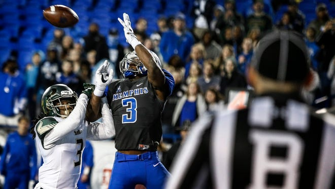 A back judge watches as University of South Florida defender Deatrick Nichols (left) appears to cause a pass interference against University of Memphis receiver Anthony Miller (right) in the end zone on fourth down during fourth quarter action at the Liberty Bowl Memorial Stadium. The controversial no-call ended the Tigers comeback chances as they fall 49-42.