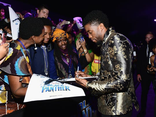 """Chadwick Boseman autographs posters at the """"Black Panther"""""""