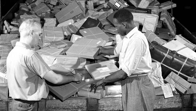 Post office employees process parcel post mail in the early 1960s.