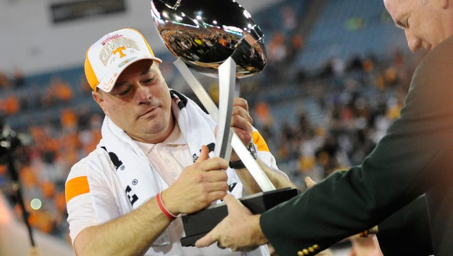 Tennessee head coach Butch Jones receives the TaxSlayer Bowl trophy following Tennessee's 45-28 victory over Iowa at EverBank Field on Friday, Jan. 2, 2015 in Jacksonville, Fla. (ADAM LAU/NEWS SENTINEL)