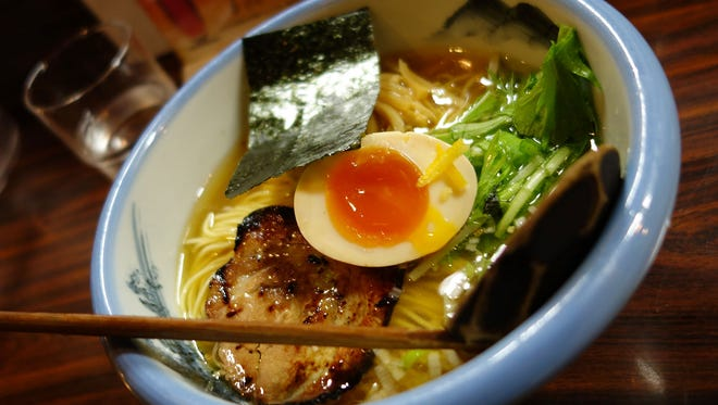 """Afuri serves what has become known as """"cafe ramen,"""" very light flavors served in smaller portions. Their clear shio ramen is accented with grated yuzu zest."""
