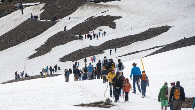 Dozens of hikers traverse a snowy path to the Hidden Lake Overlook at Logan Pass.
