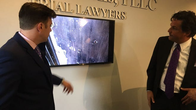 Attorneys Aaron Neglia, left, and Murray Wells, with Horne & Wells PLLC, discuss a photo of the front door of Ismael Lopez's home Wednesday, July 26, 2017.