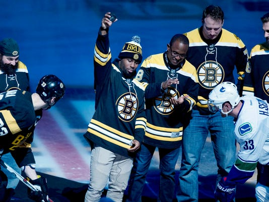 Boston Bruins' Zdeno Chara, of Slovakia, foreground left, and Vancouver Canucks' Henrik Sedin, of Sweden, foreground right, wait for the ceremonial puck drop from New England Patriots running back James White, center left, before an NHL hockey game in Boston, Saturday, Feb. 11, 2017. Standing with White are teammates, from left, defensive coordinator Matt Patricia, wide receiver Matthew Slater, tackle Nate Solder and tackle Sebastian Vollmer. (AP Photo/Michael Dwyer)
