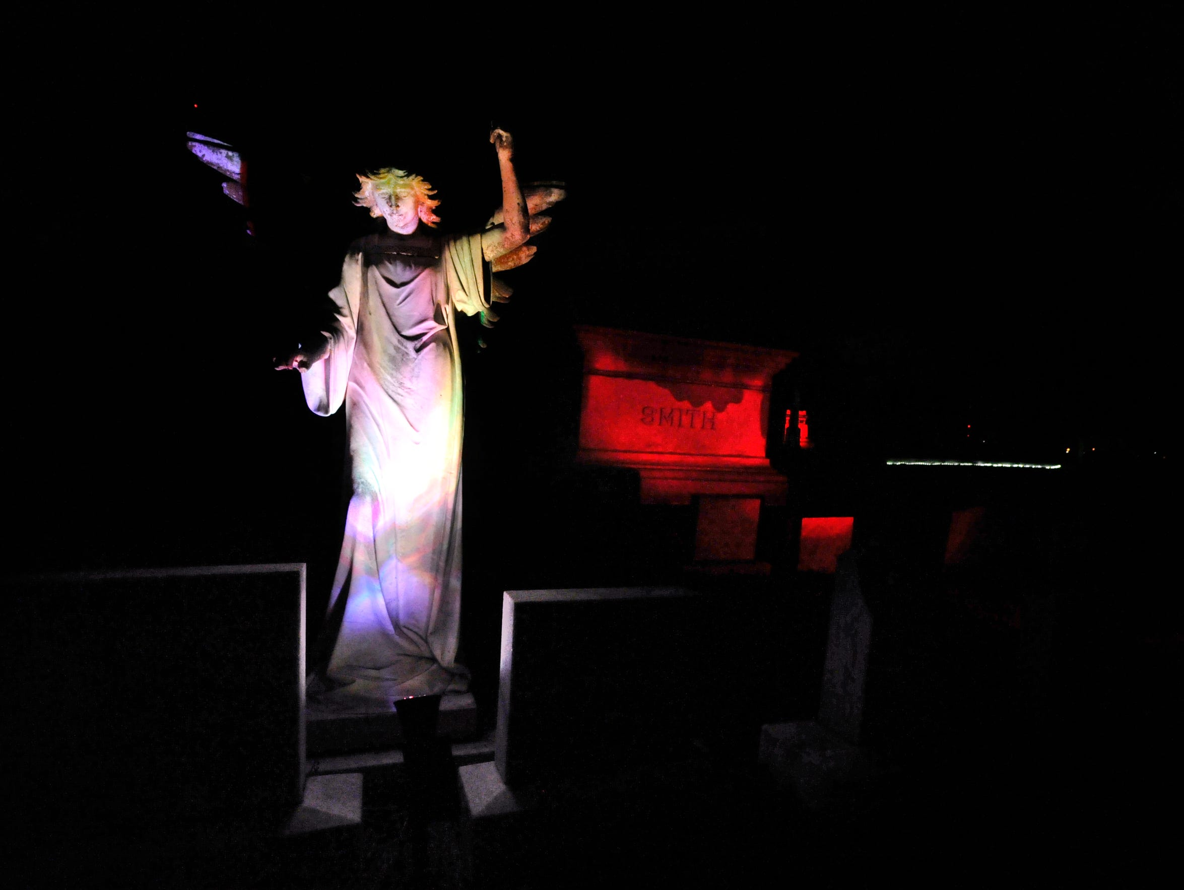 The statue of an angel and a grave marker are lit Dec.
