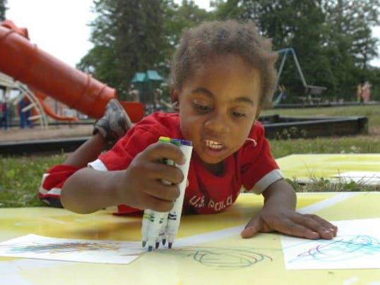 4-year-old Mike Elliot of York city uses multiple markers to draw during Yorkarts' Art in the Park program at Penn Park. (York Daily Record -- File)