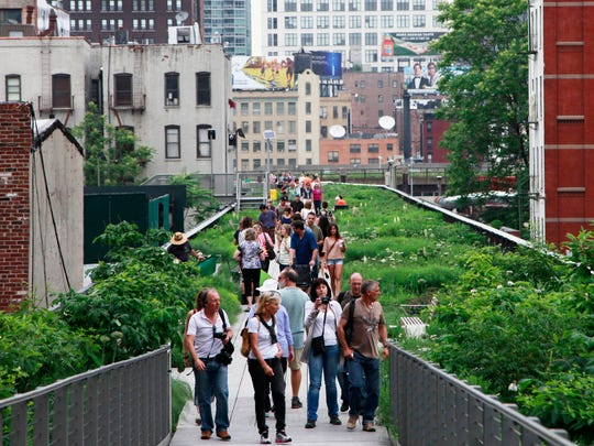 People walk on New York's High Line, the New York City park and garden which runs along a strip of old elevated track.