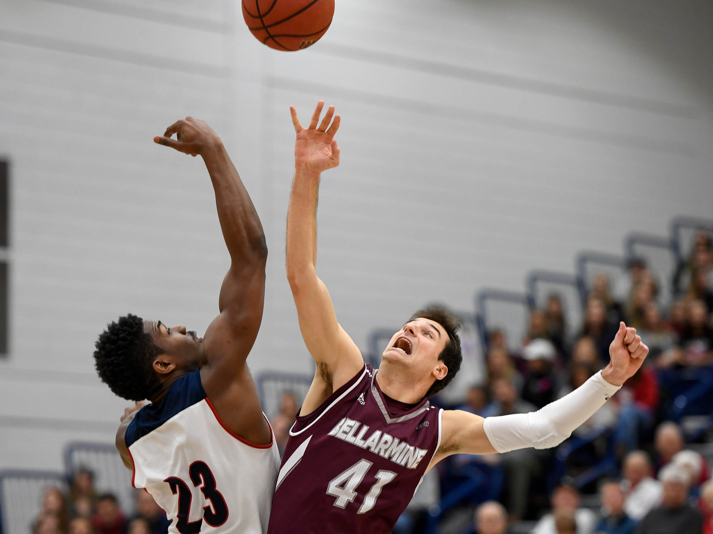 University of Southern Indiana's DayJar Dickson (23) and Bellarmine's Adam Eberhard (41) tip off as the USI Screaming Eagles play the Bellarmine Knights at USI's Physical Activities Center Saturday, February 10, 2018.