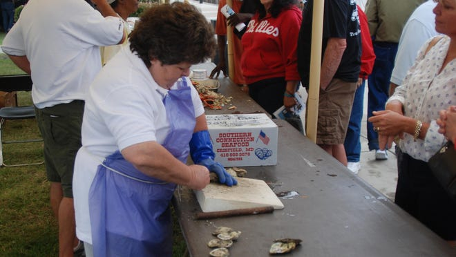 Christine Sneade shucks oysters on the half shell for sampling.
