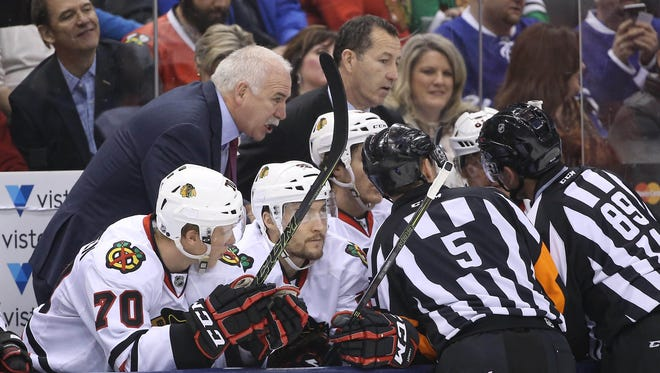 Chicago Blackhawks head coach Joel Quenneville gets an explanation from the officials about a disallowed goal by the Blackhawks in the first period as assistant coach Kevin Dineen looks on against the Toronto Maple Leafs at Air Canada Centre.