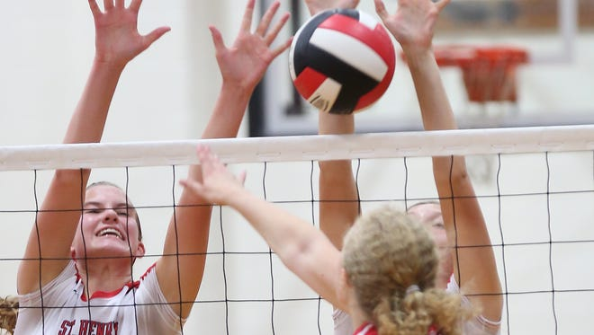 St. Henry's Janelle Tobler, No. 5, show stopping a kill attempt by Catherine Ehlman of Holy Cross last August, was state tournament MVP for the Crusaders and returns to the 2014 squad.