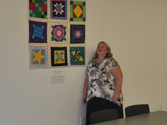 Linda Ammons smiles inside her new classroom in front of a quilt gifted to her from her first class of early college students.