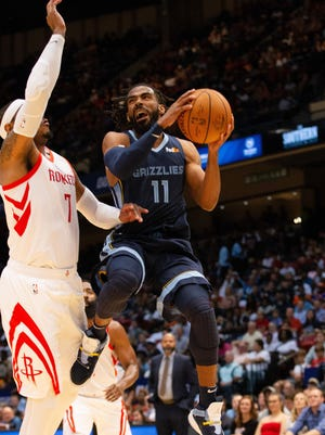Grizzlies guard Mike Conley, right, puts up a shot over the defense of the Rockets' Carmelo Anthony during the first half Tuesday.