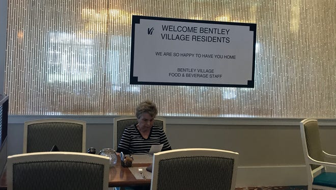 """Cheryl Lowe, a resident of Vi at Bentley Village, enjoys lunch. A """"welcome back"""" sign is behind her after the senior community evacuated to Orlando before Hurricane Irma. """"I love it,"""" she said of the community."""