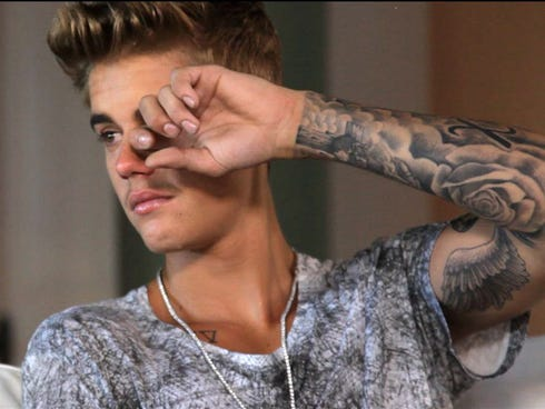 Justin Bieber swipes at his eyes in 'Believe,' opening Christmas Day 2013.