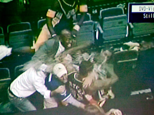 In this video framegrab shown during a news conference, in Pontiac, Mich, Wednesday, Dec. 8, 2004, by Oakland County (Mich). prosecutors, spectator John Green, center with baseball cap , holds Indiana Pacers' Ron Artest during a fight between fans and several Indiana players, at the Palace in Auburn Hills, Mich., Nov. 19, 2004.  Oakland County (Mich.) prosecutor David G. Gorcyca announced Wednesday, that five Pacers players and seven fans were charged Wednesday in one of the worst brawls in U.S. sports history. Artest, Stephen Jackson, David Harrison and Anthony Johnson all were charged with one count of assault and battery, a misdemeanor that carries a maximum penalty of about three months in jail and a fine of up to $500. Jermaine O'Neal, a three-time NBA All-Star, was charged with two counts of assault and battery.Green is one of the seven spectators who were charged in the brawl. (AP Photo/Oakland County Prosecutor)
