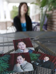 Photos of Nengmy Vang placed on a table with Naly Vang in the background at The Women's Community in Wausau.
