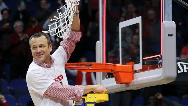 Louisville head coach Jeff Walz cut down the net after their win over Oregon State during their NCAA Elite 8 matchup at Rupp Arena in Lexington.    