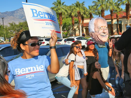 People take photos with a man in a Bernie Sanders mask before the start of Sanders' campaign rally in Cathedral City, May 25, 2016.