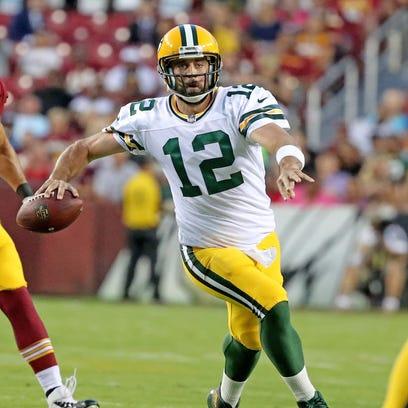 Green Bay Packers quarterback Aaron Rodgers (12) scrambles
