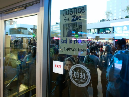 A protester holds a sign against the door of the Golden 1 Center during a demonstration, Thursday, March 22, 2018 in Sacramento, Calif. The march to decry this week's fatal shooting of an unarmed black man, wound its through downtown Sacramento, disrupting rush hour traffic, blocking Interstate 5 for awhile and forcing the Golden 1 Center to lock its doors ,leaving hundreds of ticket holders unable to enter. The Kings NBA basketball game against the Atlanta Hawks was delayed for a while but play was started with hundreds of empty seats. (AP Photo/Rich Pedroncelli)