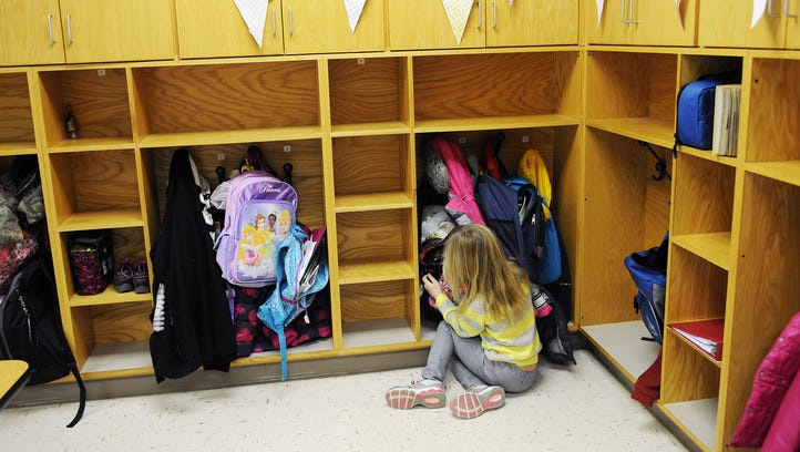 A girl zips up her backpack in front of the cubby holes