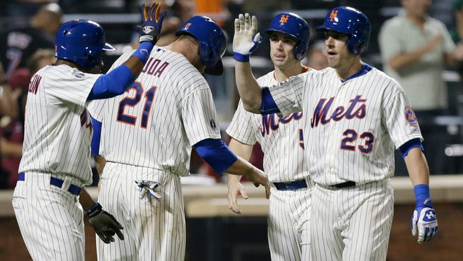 The Mets' Taylor Teagarden, right, celebrates with David Wright (5), Lucas Duda (21) and Curtis Granderson after hitting a grand slam in the sixth inning against Milwaukee on Tuesday.