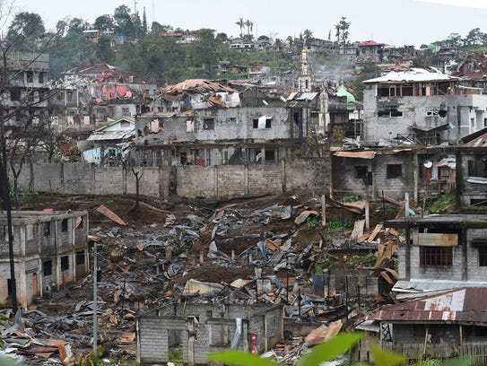 Destroyed buildings are seen from a government sniper's
