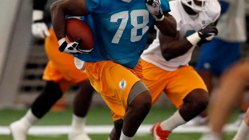 Miami Dolphins defensive end Terrence Fede runs with the ball after intercepting a pass during mini-camp at Miami Dolphins Training Facility on June 17.