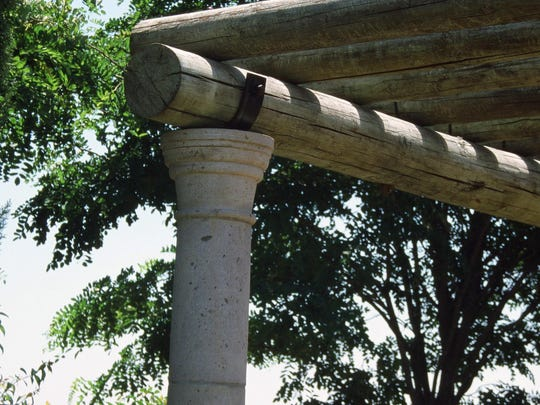 The clean look of grey-green color of pressure treated peeler cores are anchored but custom made strap steel cradles set into cantera stone columns.