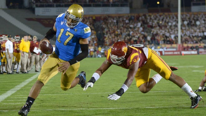 UCLA Bruins quarterback Brett Hundley (17) eludes Southern California Trojans defensive end Leonard Williams (94) to score on a 4-yard touchdown run in the third quarter at Los Angeles Memorial Coliseum in 2013.