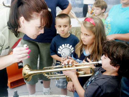 Shelby Strickland, director of education and community with the Nashville Symphony, teaches Lucca Silva the first steps in playing a trumpet during the Regions Free Day of Music at the Schermerhorn Symphony Center in 2008.  Looking on are Blake Smith and Faith Matzoll.