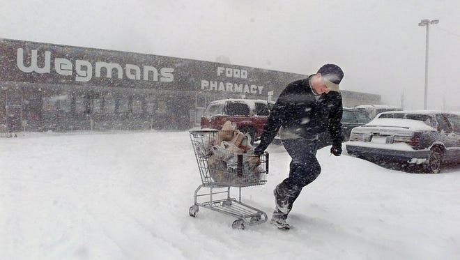 """-  -Chris Gamble of Rochester makes his way through the snow with his groceries at the Wegmans on the East Ave. Gamble tried to go to work, but was sent home. The snow was not keeping him from stocking up on goodies for a """"snowed in"""" party tonight. Chris lives in the Park Ave. area. Wegmans had a few brave people shopping, but was thinking of closing down early.(Democrat and Chronicle, Photo by Andrea Melendez 030499 Rochester)"""