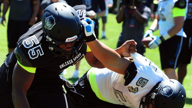 Defensive lineman Da'Shawn Hand (55) battles offensive lineman Toa Lobendahn (54) during the Lineman Challenge session of the 'The Opening' at Nike World Headquarters on July 3, 2013.