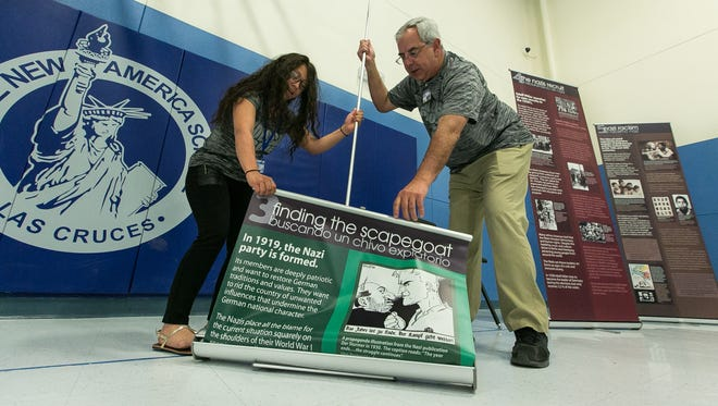 """New America School student Nancy Martinez, 18, and teacher Ray Murray work together on Friday, March 11, 2016, to set up a informative Holocaust display called """"Choices"""" sponsored by the New Mexico Human Right Projects in Albuquerque. The display tells the story in words and pictures of how Nazi Germany was turned into a killing machine."""