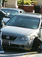 Police look at  bullet holes in the windshield of the