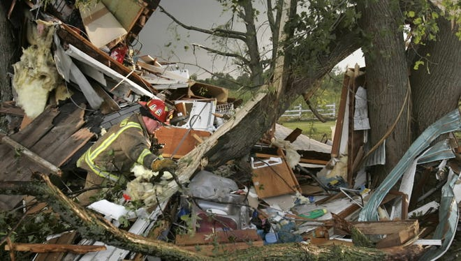 A firefighter searches the debris of a house looking for survivors after a tornado ripped through a neighborhood north of Stoughton on Aug. 18, 2005. Firefighters found a cat and dog alive while searching the rubble. No humans were home when the tornado hit.